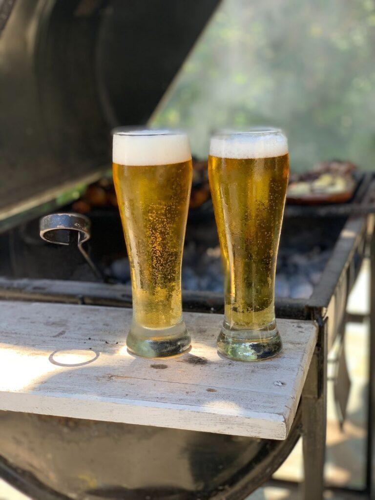 Na imagem temos dois copos pilsen, um dos tipos de copos para cerveja, em cima do tablado de uma churrasqueira.