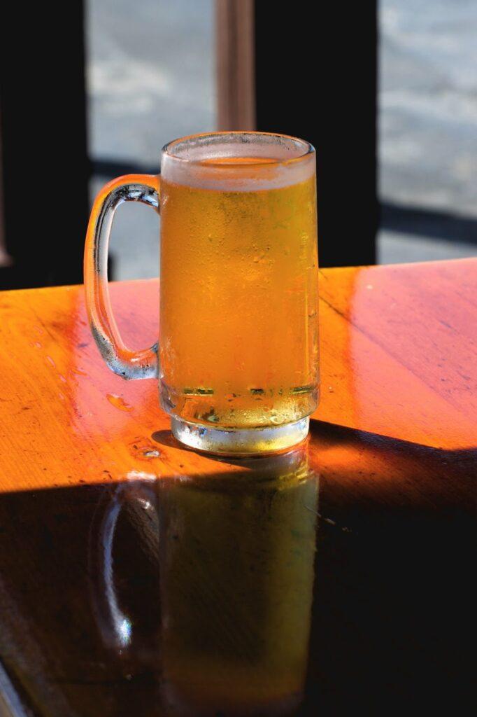 Na imagem temos uma caneca, um dos tipos de copos para cerveja, em cima de uma mesa.