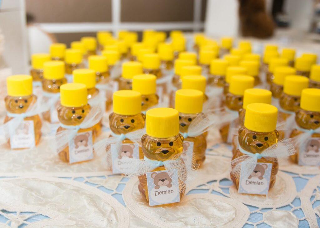 várias lembrancinhas de ursinhos com mel dentro, com tampinhas amarelas