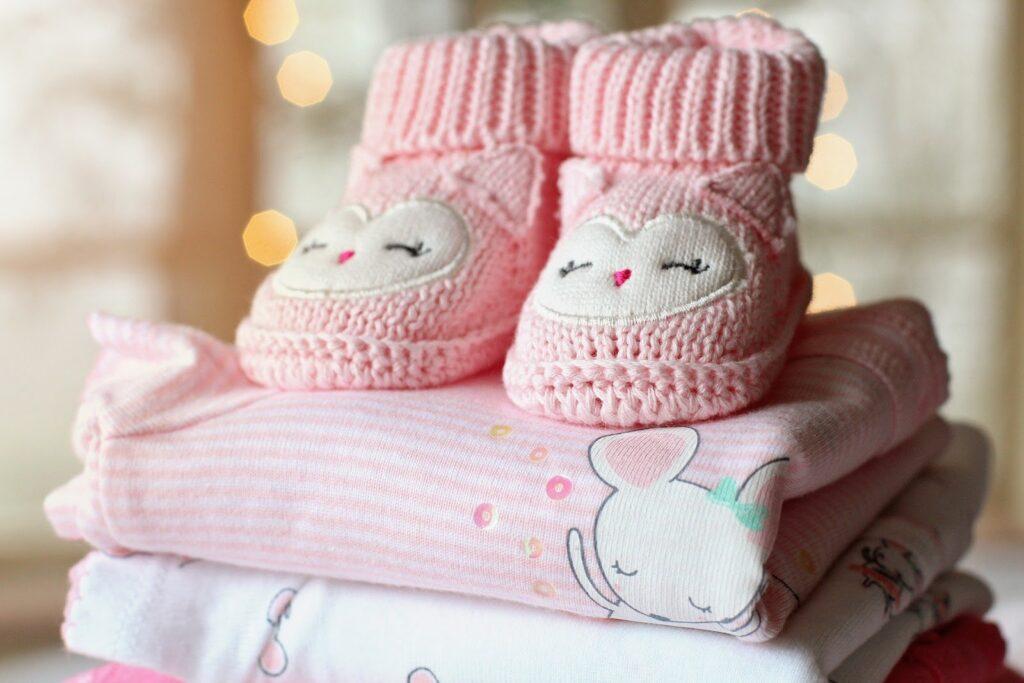 Foto de dois saptinhos de lã para bebês, em cima de lencinhos rosa