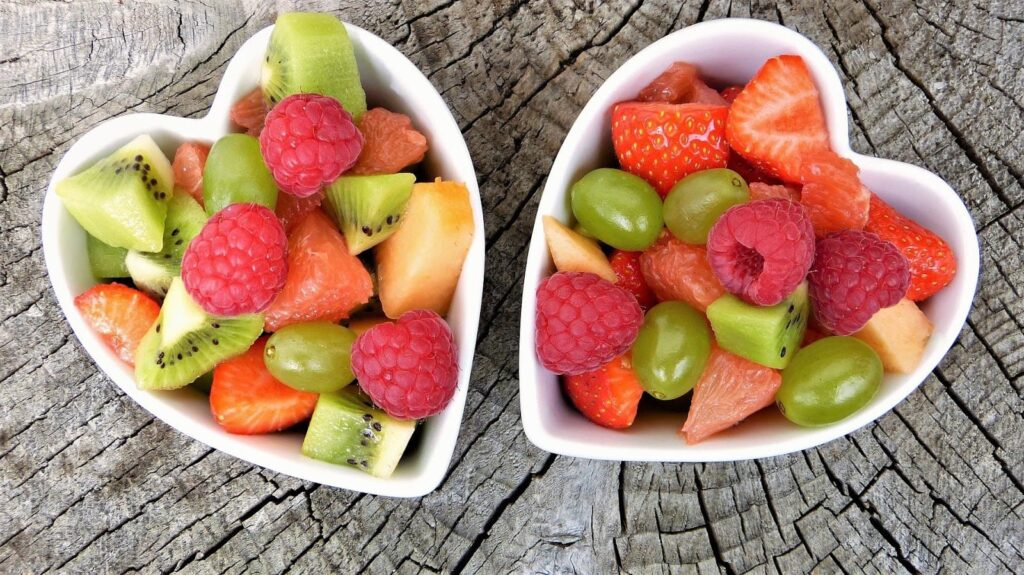 copos de coração com salada de frutas.