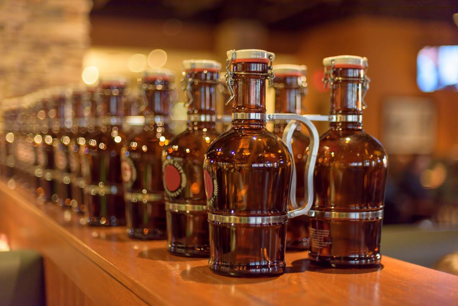 Na imagem, temos vários growlers de vidro, utilizados para armazenar cerveja, em cima de um balcão de madeira