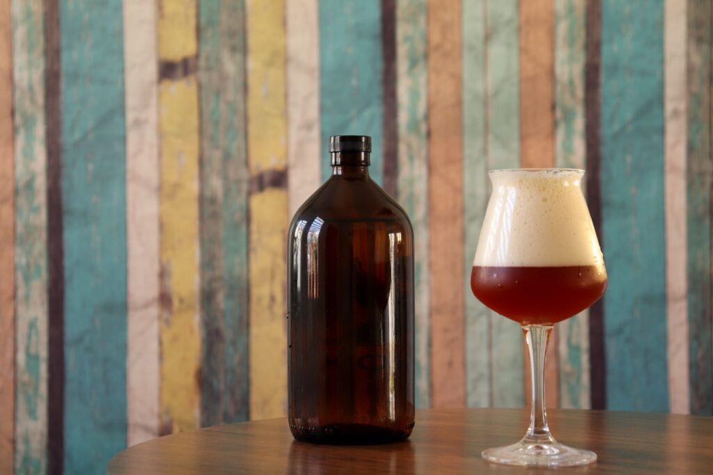 Na imagem, temos uma taça cheia de cerveja ao lado de um growler, ambos em cima de um barril de madeira com sementes de lúpulo espalhadas.