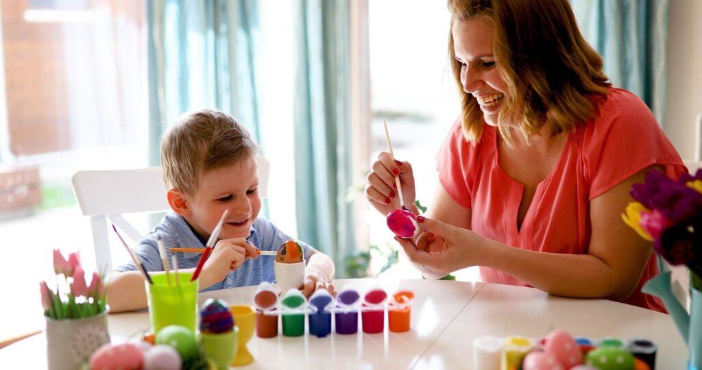 Mãe e filho pintando ovos com tinta