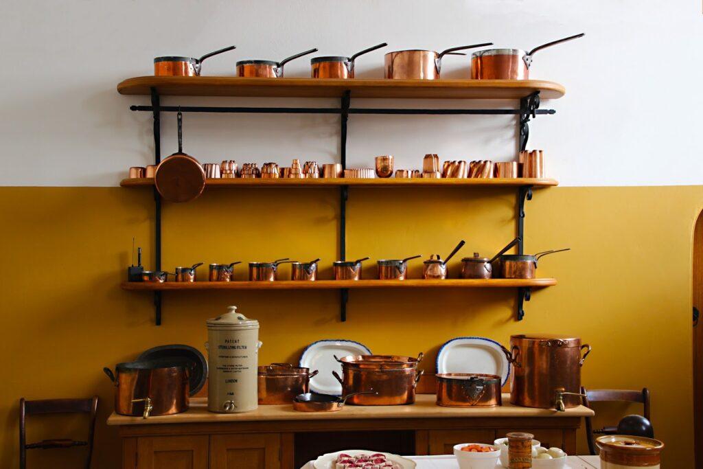 prateleira com diversas panelas de cobre, bem arrumadas