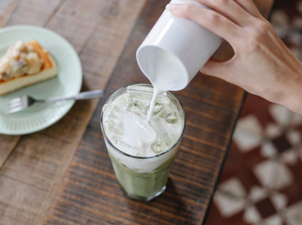 mulher colocando creme de leite em um copo de suco verde