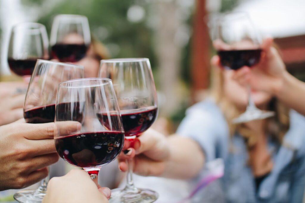 close de brinde com taças de vinhos em um ambiente aberto