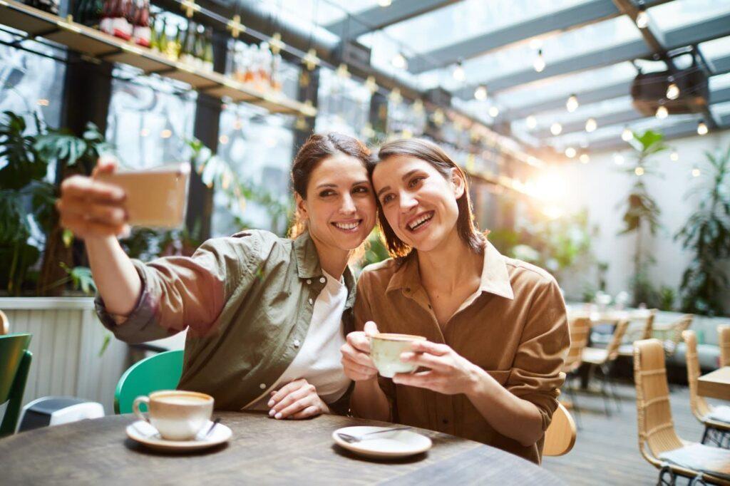 Duas mulheres sentadas tirando uma selfie