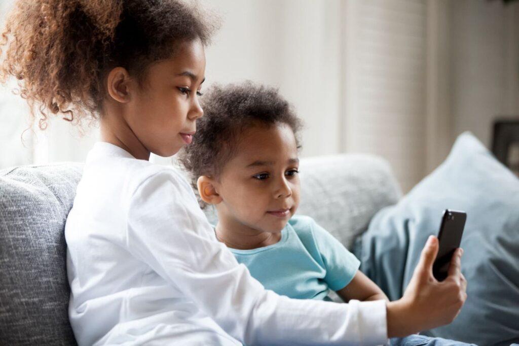 duas crianças vendo algo no celular
