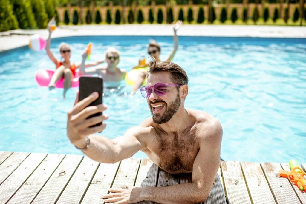 homem com amigos tirando uma selfie na piscina