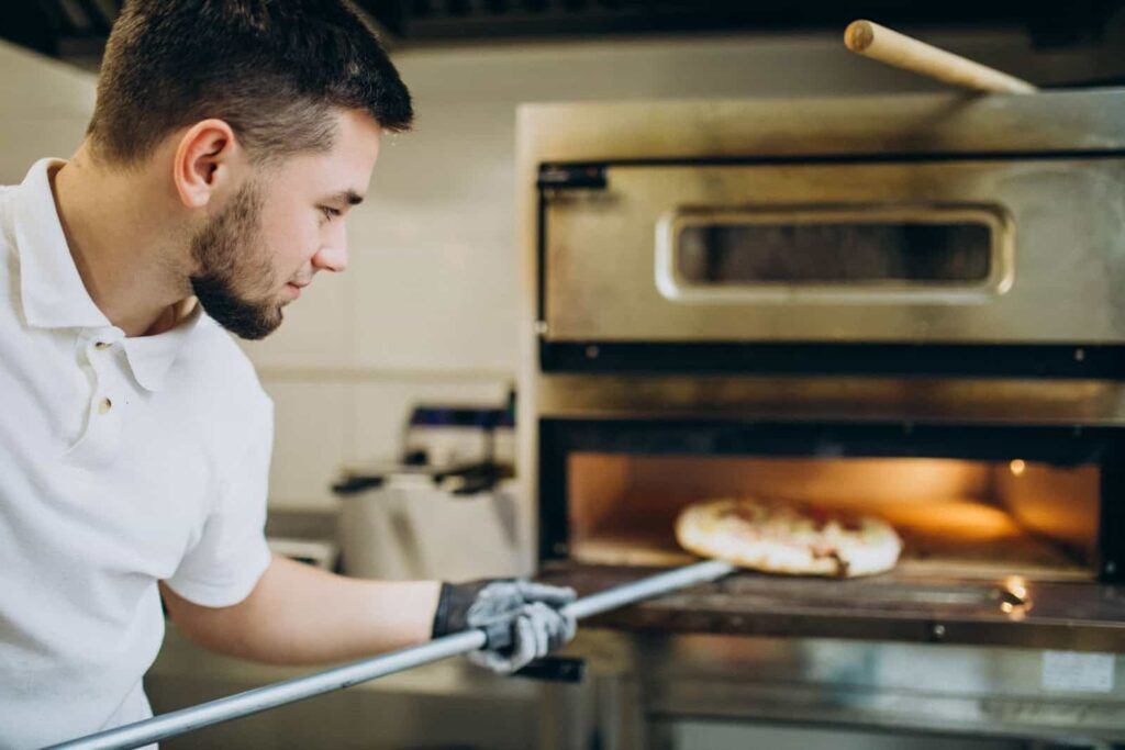 Homem de camisa branca colocando uma pizza para assar em forno.