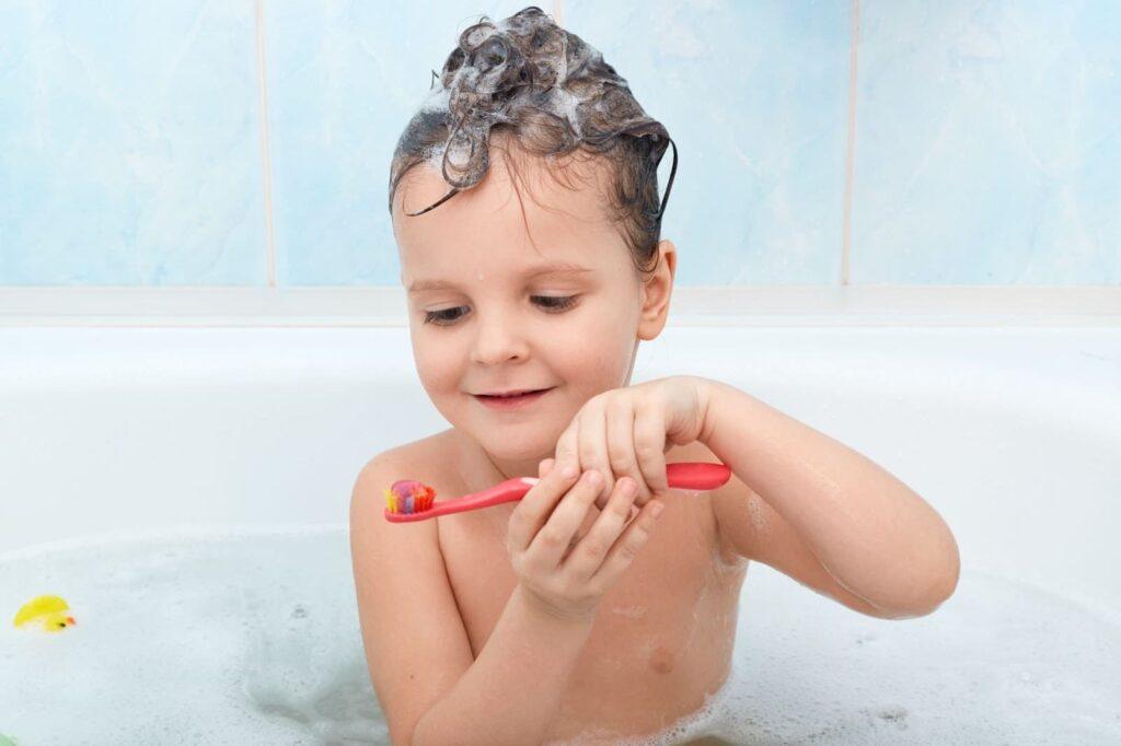 criança em uma banheira segurando escova de dente com pasta