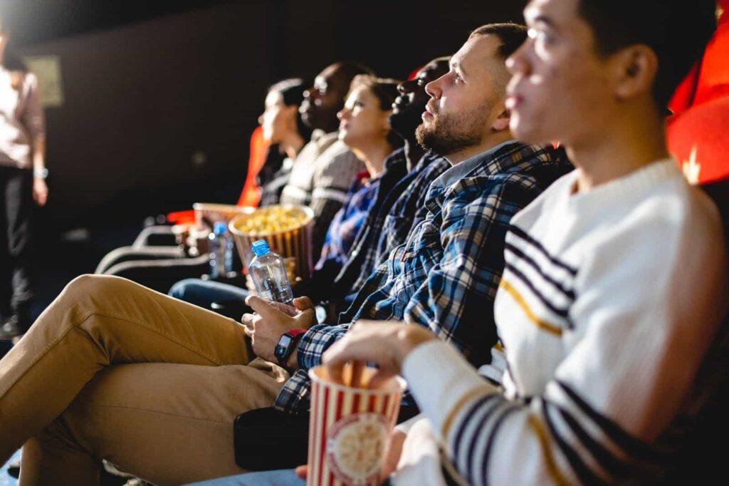 Cinco pessoas diversas sentadas em poltronas de uma sala de cinema comendo pipoca ou segurando garrafas de água.