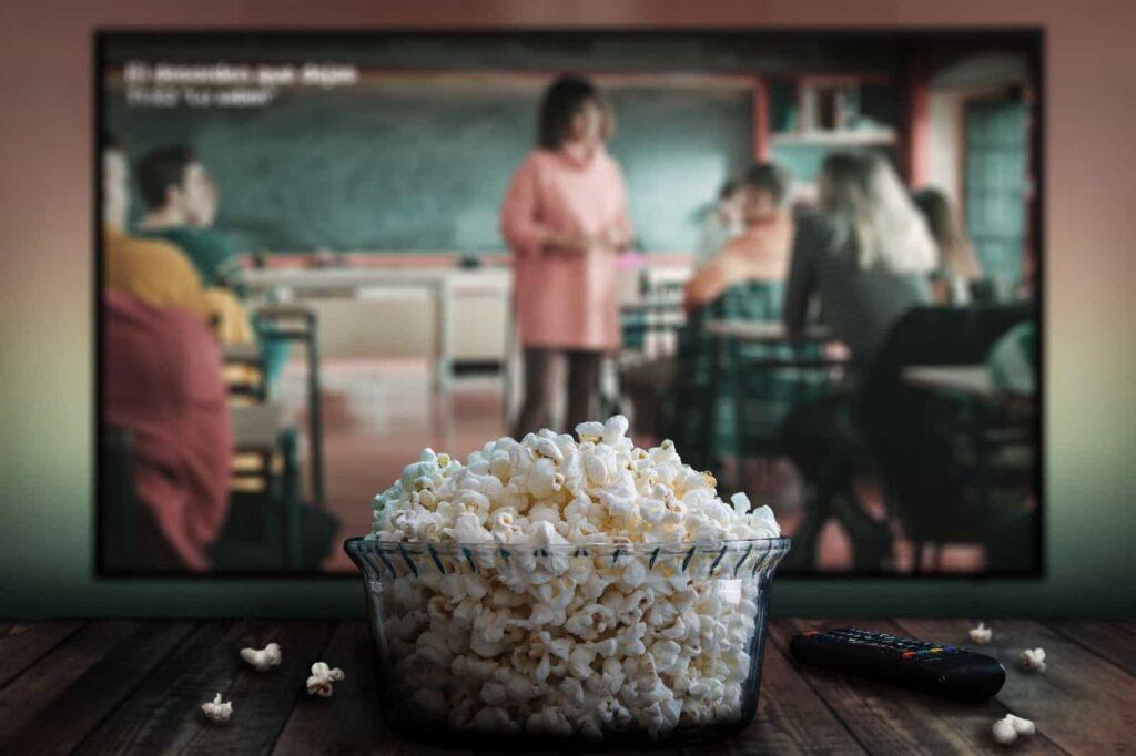 Filme com uma professora de blusa rosa e alunos sentados em suas cadeiras numa sala de aula sendo reproduzido em uma tela ao fundo. À frente, uma tigela de vidro com pipoca e ao lado direito, um controle remoto.
