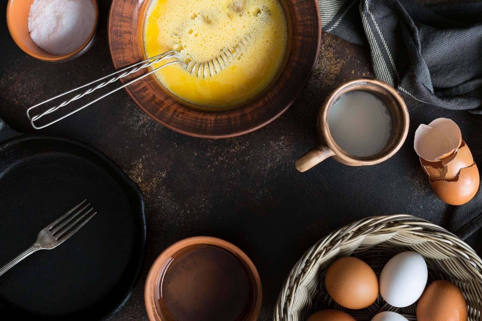 Na imagem, o preparo de receitas com ovos tendo um vasilhame com ovos batidos pelo batedor de metal, duas canecas em tons de marrom e uma cesta de ovos