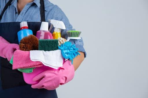 pessoa com camisa azul e avental preto segurando uma série de produtos de limpeza demonstrando como ser uma faxineira eficiente