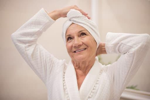 Uma senhora idosa com roupão branco e toalha branca na cabeça para transmitir a ideia de autocuidado com no poo e low poo