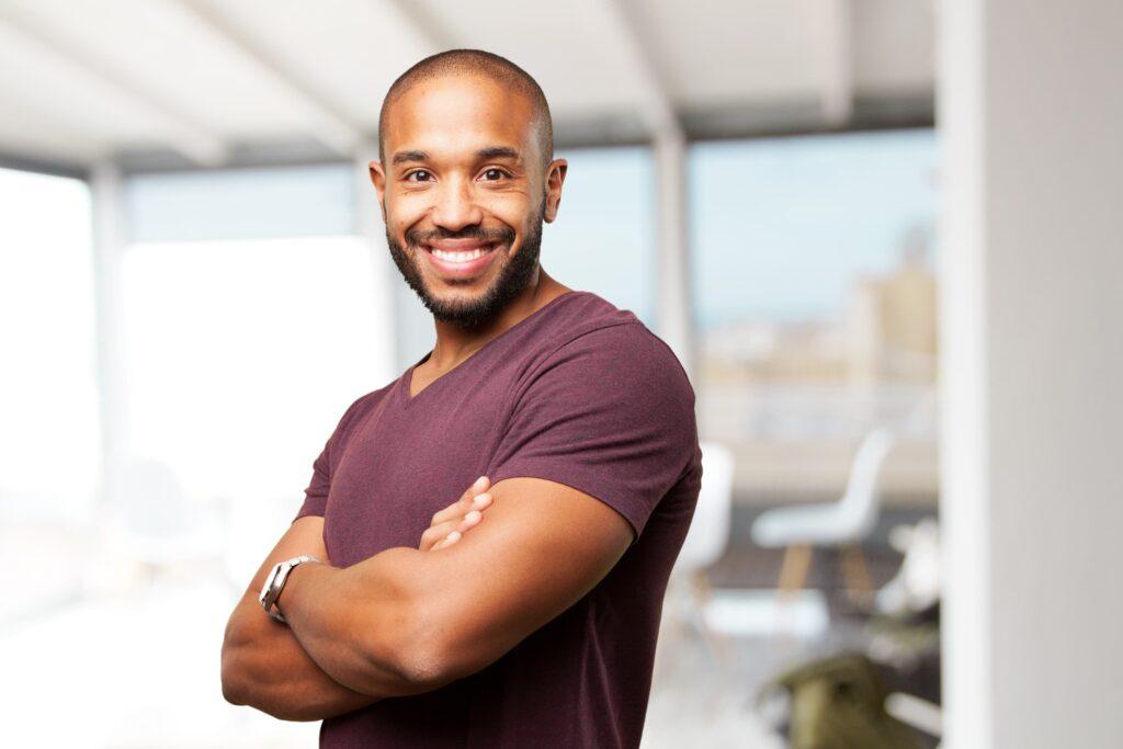 Homem negro de camisa bordô e braços cruzados sorrindo para representar a saúde masculina