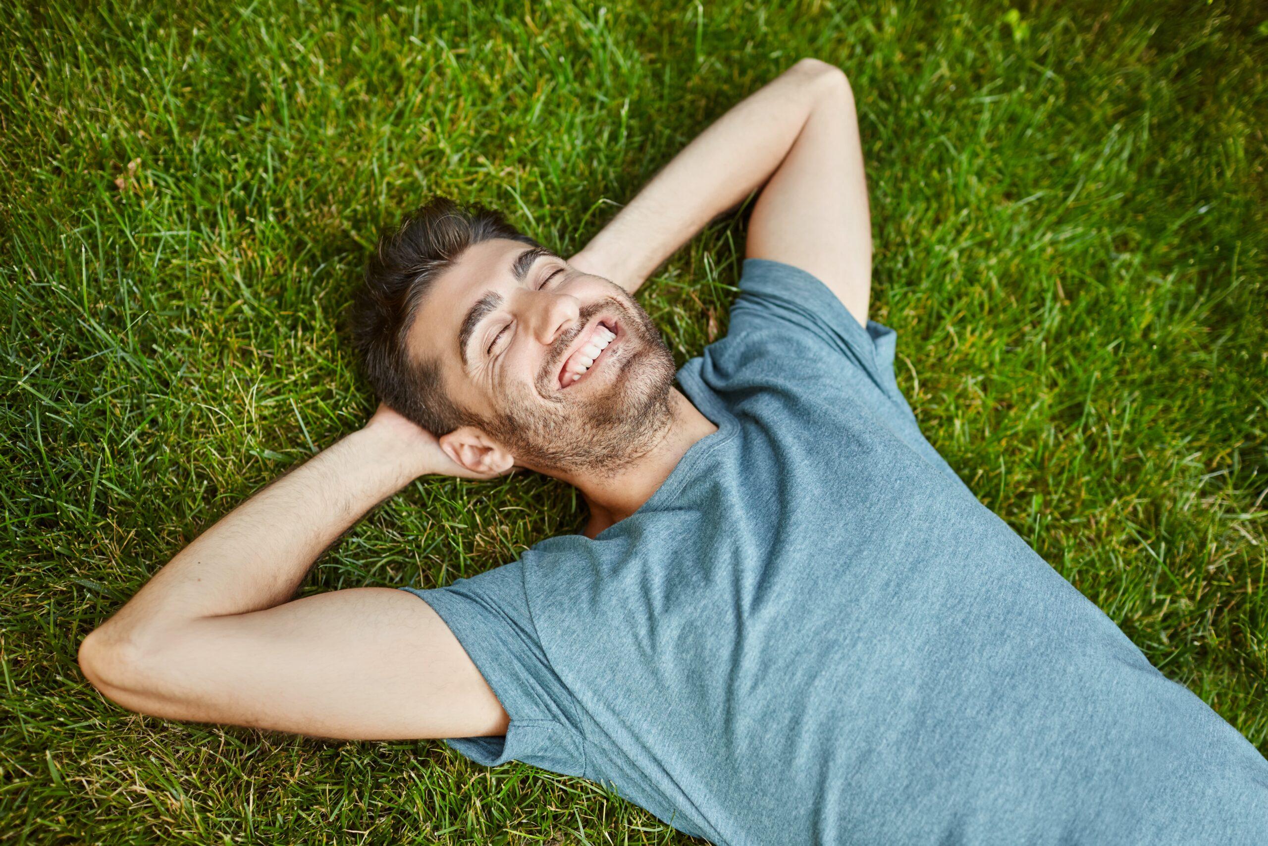 Homem deitado na grama e sorrindo para representar a importância dos cuidados com a saúde masculina