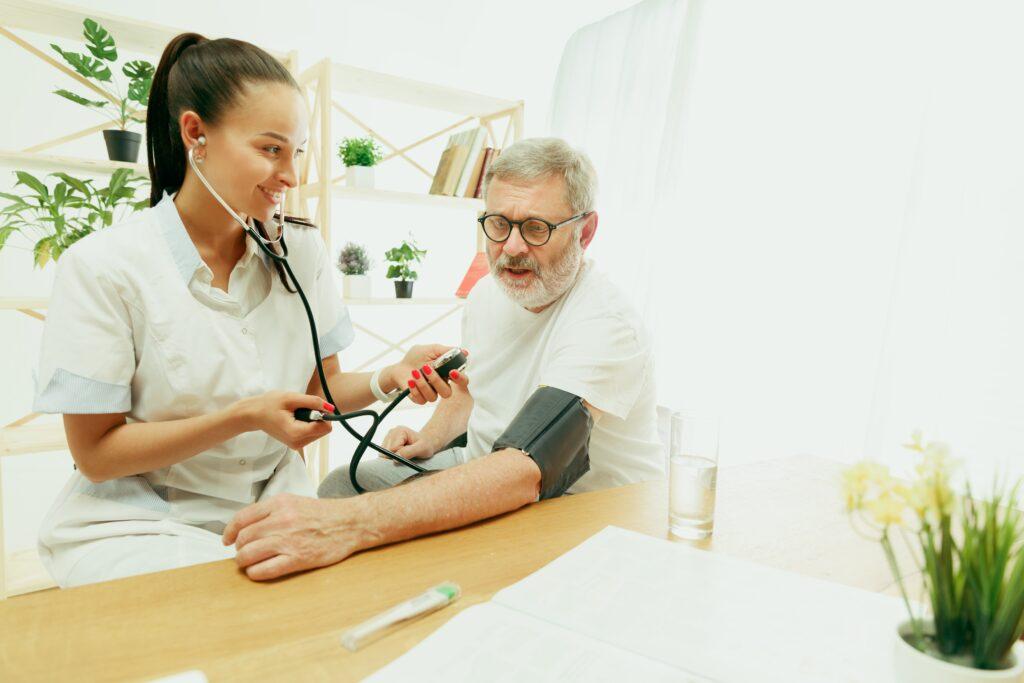 Enfermeira aferindo pressão de um senhor idoso para representar os cuidados com a saúde masculina.